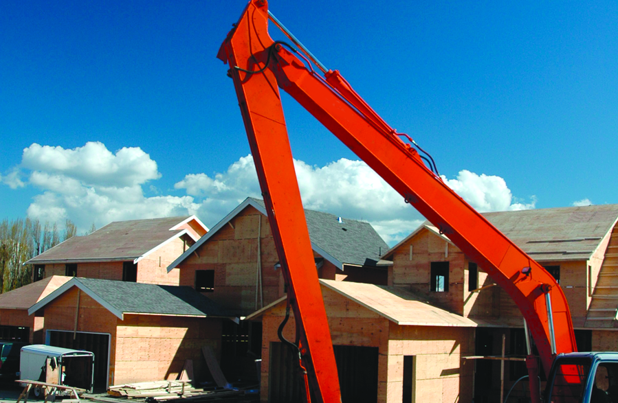Red excavator in front of houses under construction