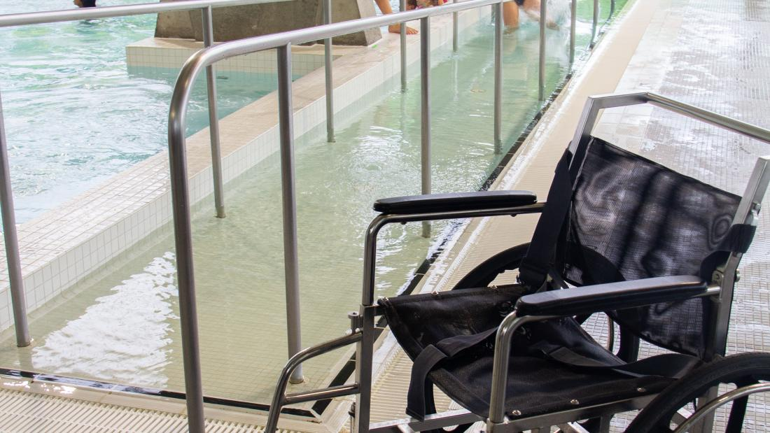 A wheelchair beside a pool