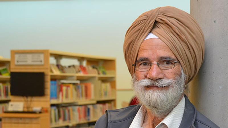 senior in turban reading a book