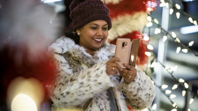 Woman taking photos with a phone at Christmas time.