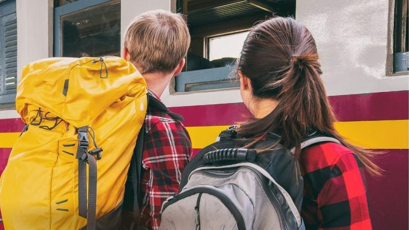 Young man and woman with backpacks in a train station, getting ready to board train