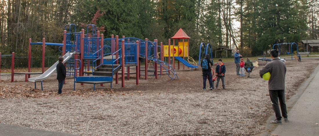 a blue playground with people standing around