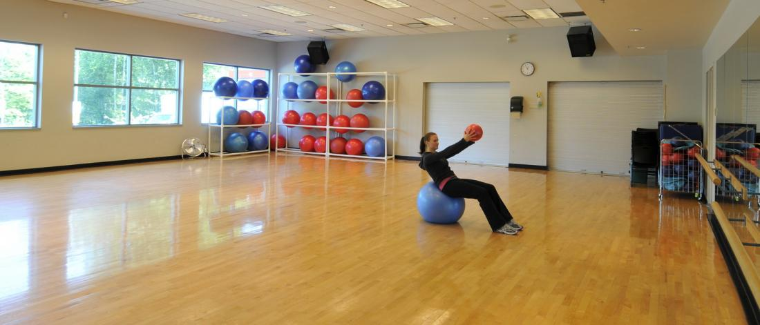 A girl balances equipment on a stability ball