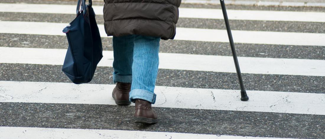 A person with a cane walks in a crosswalk