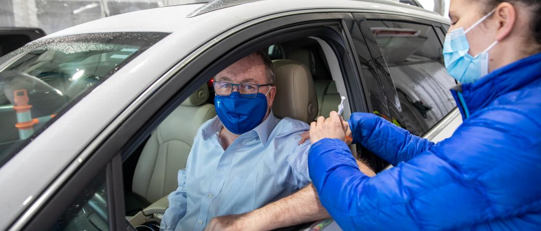 Mayor McCallum receiving COVID-19 Vaccine from Fraser Health staff member while seated in a car