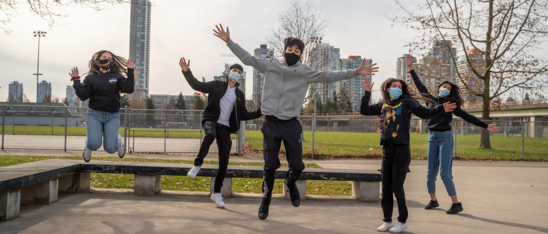 Group of 5 youth jumping with masks on