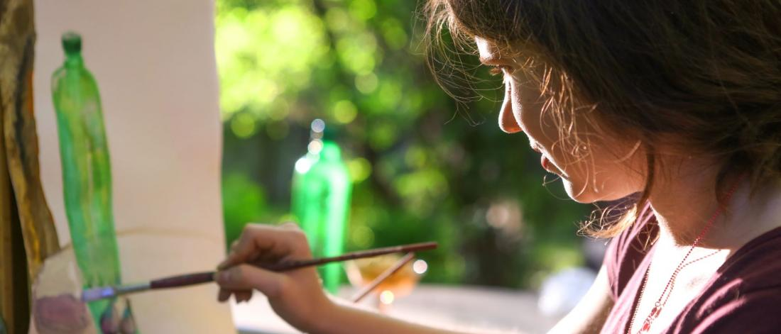 Young girl paints a picture outdoors