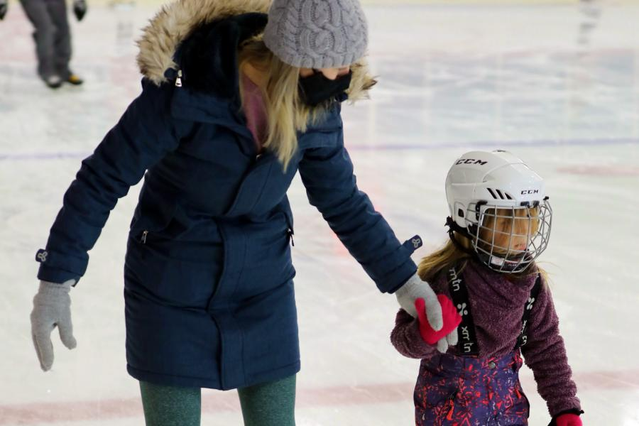 A mother and her child skating at the arena.