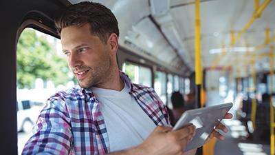 Man on Bus Holding Tablet