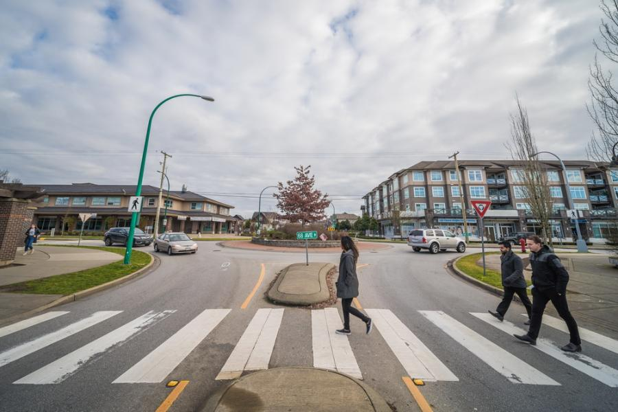 3 people using a crosswalk at a roundabout