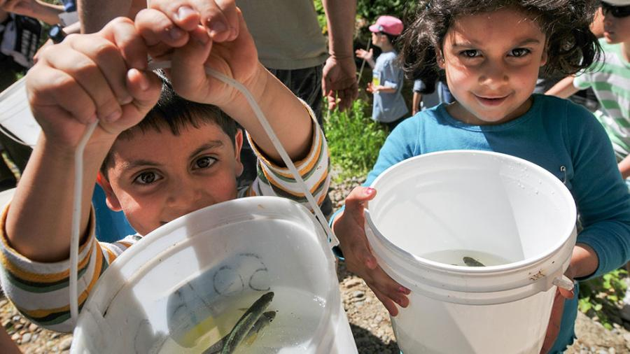 Kids with buckets for fish release