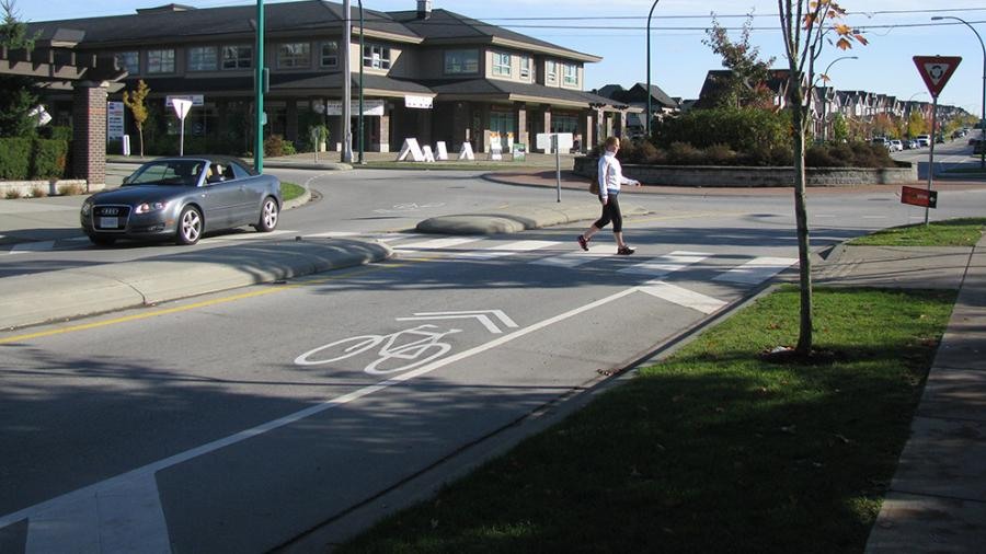 Person walking across a crosswalk in Surrey.
