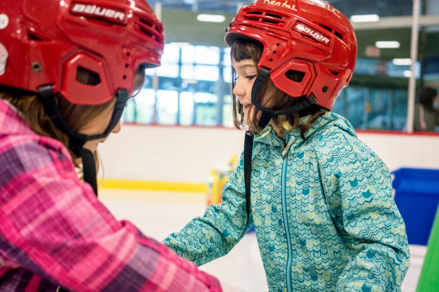 Two girls with red helmets at the ice rink